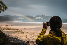 Rear View Of Woman In Raincoat Photographing Rainbow At Beach