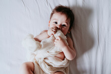 Cute Baby Boy Holding Towel While Lying On Bed In Bedroom At Home