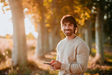 Smiling Man Using Mobile Phone While Standing At Forest