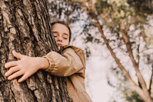 Cute Girl With Eyes Closed Hugging Tree At Park