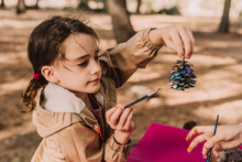 Cute Girl Holding Pine Cone While Coloring By Sister At Park