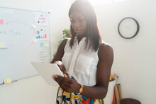Businesswoman Using Digital Tablet While Standing At Office
