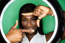 Smiling Young Woman Making Finger Frame Against Green Background
