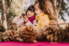 Smiling Cute Sisters Coloring Pine Cone At Picnic Table In Park