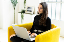 Thoughtful Young Woman Blogging While Sitting With Laptop On Chair At Bright Home