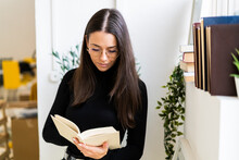 Beautiful Female Brunette Reading Book While Standing At Home