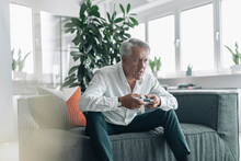Senior Businessman Playing Video Game With Concentration While Sitting On Sofa At Office