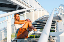 Smiling Woman Sitting On Staircase At Park