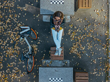 Woman Using Smart Phone While Sitting Amidst Chess Tables In Park During Autumn