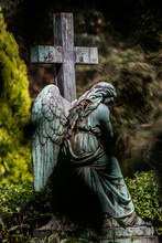 Weathered Statue Of Angel Sitting Beside Cross In Cemetery