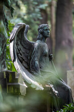 Weathered Statue Of Angel Sitting At Edge Of Tomb In Cemetery