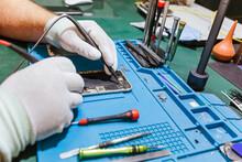 Technician Examining Damaged Mobile Phone At Workbench At Repair Shop