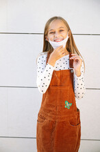 Smiling Girl Wearing Protective Face Mask Standing Against Wall On Sunny Day