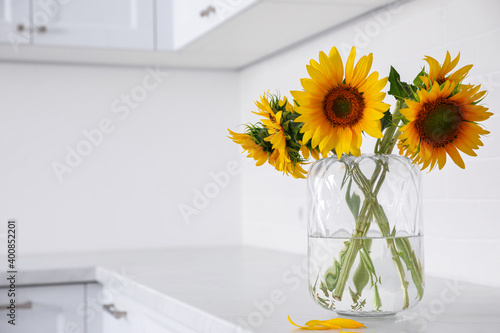 Fototapeta Bouquet of beautiful sunflowers on counter in kitchen. Space for text obraz