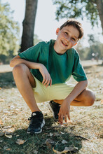 Boy Crouching In Pubic Park On Sunny Day