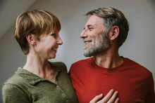Smiling Couple Looking At Each Other While Standing At Home