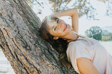 Smiling Mature Woman With Hands In Hair Lying On Tree Trunk During Sunny Day