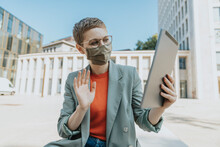 Woman Wearing Protective Face Mask Doing Video Call With Digital Tablet Sitting On Street