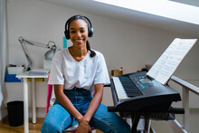 Smiling Teenage Girl With Wearing Headphone Sitting On Chair At Home