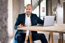 Man Wearing Suit Using Laptop And Mobile Phone While Sitting At Office