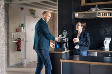 Smiling Business People Taking Coffee Break While Standing At Cafeteria In Office