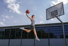 Young Male Athlete Practicing Dunking Ball In Basketball Hoop On Sunny Day