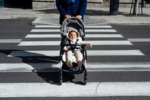 Father With Baby In Baby Stroller Crossing Road In City