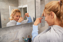 Mature Woman Looking In Mirror Cutting Her Own Hair At Home