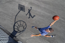 Young Man Dunking Ball In Hoop While Playing Basketball On Sunny Day