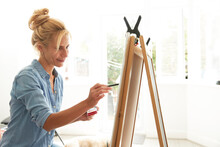 Smiling Mature Woman Painting On Paint Board At Home