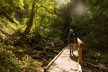 Female Hiker Crossing Wooden Bridge Stretching Over Forest Stream In Summer