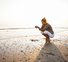 Beautiful Young Woman Crouching While Holding Sand On Shore At Beach During Sunset