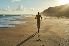 Man Jogging On Sand At Beach During Sunset