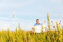 Male Entrepreneur Holding Blueprint While Standing Against Wind Turbines On Field