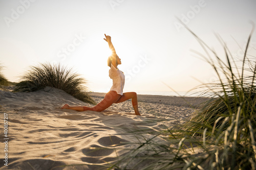Young woman practicing yoga on sand at beach during sunset
