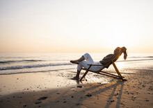 Smiling Young Woman Relaxing On Folding Chair At Beach Against Clear Sky During Sunset