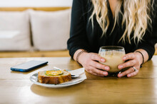 Mid Adult Woman Having Coffee And Cake While Sitting At Coffee Shop