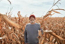 Smiling Farmer Standing At Corn Field During Sunny Day