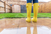 Close-up Of Woman Standing In Back Yard During Rainy Season