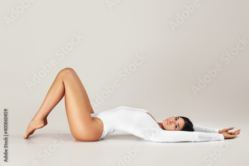 Fotografie, Obraz beautiful healthy woman with perfect body and legs in white bodysuit posing over studio background