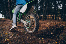 Male Teenager Spinning Motorcycle Tire While Blowing Dirt In Forest