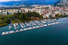 Switzerland, Canton Of Ticino, Locarno, Helicopter View Of Harbor Of Lakeshore Town At Dawn