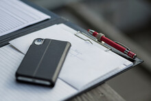 Clipboard With Smart Phone And Pen On Desk