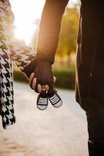Heterosexual Couple Holding Baby Booties In Park During Autumn