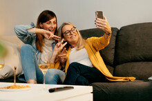 Smiling Mother And Daughter Making Peace Sign While Taking Selfie Through Smart Phone At Home