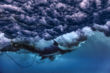 Male Surfer Diving Underwater With Surfboard Below Waves At Maldives