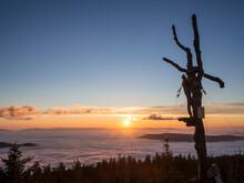 Bare Tree On Summit Of Heugstatt Mountain With Sun Setting In Background