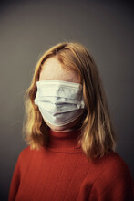 Teenage Girl Covering Entire Face With Protective Face Mask While Standing Against Gray Background