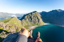 Man Wearing Sports Shoe Sitting On Mountain At Ryten, Lofoten, Norway