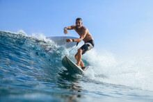 Man Balancing While Surfing In Sea Against Clear Sky